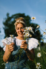 Blurred Young Woman In Casual Clothes Enjoying Smell Of Fresh Chamomiles While Collecting Flowers On Green Meadow In Spring