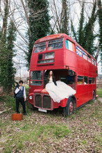 Bride In Wedding Dress Sitting On Hood Of Old Double Decker Bus And Groom In Classy Tuxedo Standing Near Suitcase In Wood
