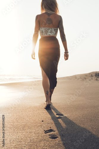 Back view of unrecognizable slim barefoot young woman in black dress walking on wet sand near waving sea while enjoying seascape on sunny day in summer - 364556829