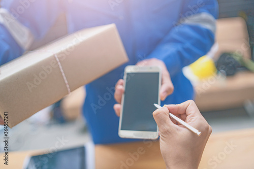 Delivery,mail and shipping,delivery man Checking Portable Device with Asian woman sign in digital Smartphone before receiving parcel or receive package,she appending signature in mobile phone at home Fototapete
