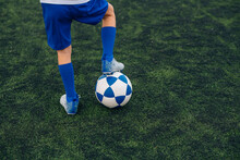 High Angle Of Faceless Child In Blue Shorts And Cleats With Ball Standing Alone On Green Court While Playing Football At Modern Stadium