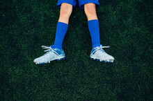 Top View Unrecognizable Child In Blue Shorts And Boots With Knee Socks Lying Alone On Green Court After Playing Football At Modern Stadium