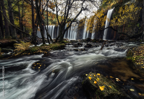 Amazing view of waterfall cascade and stream flowing through autumn forest with colorful yellow leaves on overcast day - 364558284