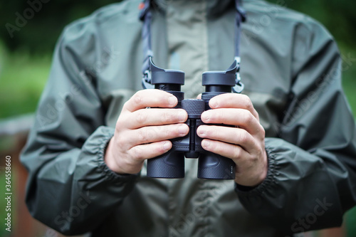 Stampa su Tela Close up of a man dressed in a hunter jacket holds binoculars in his hand