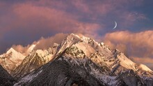 Magnificent View Of Mountains Covered With Snow At Sunset With The Moon In The Sky