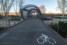 Perspective View Of Paved Wooden Bike Path Going To Futuristic Gallery In Park In City During Evening