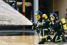 Faceless Firemen In Safety Helmets And Protective Uniform Extinguishing Fire With Water Hose During Training On Sunny Day