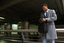 Handsome African-American Man In Suit Checking Bag