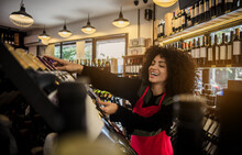 Pretty Curly Woman In Red Apron Composing Bottles On Wine On Shelf Working In Market.