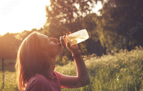 Photo Girl drinking water with lemons from clear plastic bottle in contrast light duri
