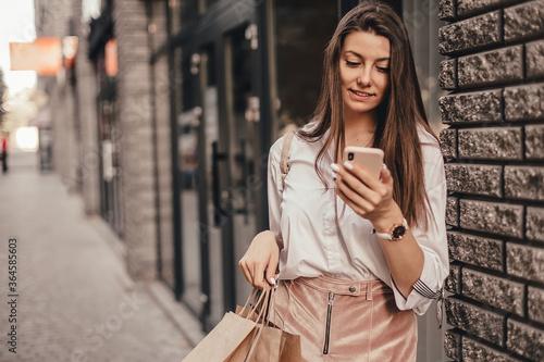 Fototapeta Beautiful fashionable woman using phone walking near mall with shopping bags. obraz
