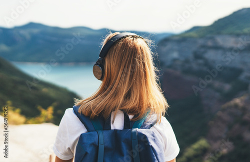 Foto back view girl tourist with light hair dreams listening to music in headphones s