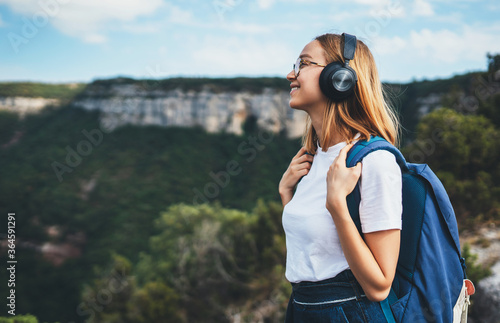 Canvastavla positive young traveler girl with headphones and backpack stands on top of mountain, active tourist woman hiking enjoys beautiful landscape and