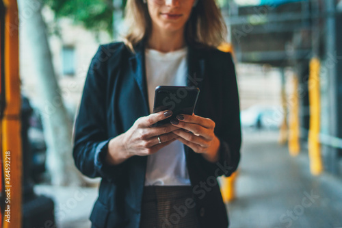 Fényképezés Woman manager in black suit walking in city and working on smartphone, businessw