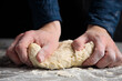 Thin male hands knead the dough for bread, pasta or pizza, close up. Closeup hand of chef baker kneading a dough