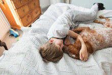 Affectionate Boy Cuddling Dog ...
