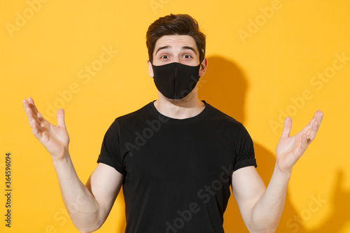 Stampa su Tela Shocked young man guy in black t-shirt face mask isolated on yellow wall background studio portrait
