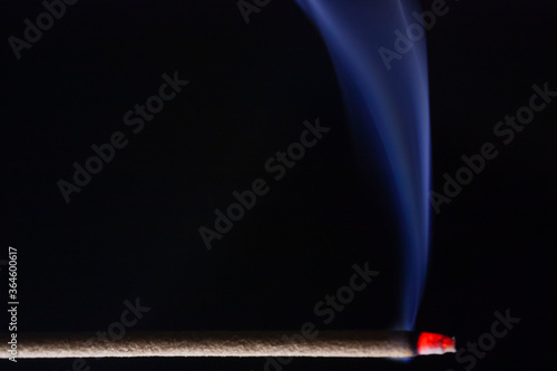 Fotografiet Close-up picture of burning incence releasing blue fragrance smoke at night