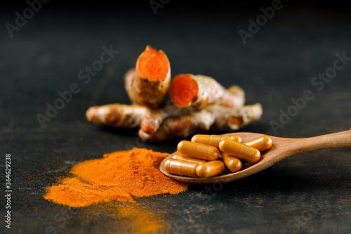 Fotografía Turmeric powder in capsules, with fresh turmeric heads as a backdrop
