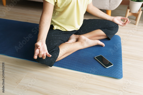 Fototapeta Hand of woman in lotus pose while sitting at mat yoga with smartphone obraz na płótnie