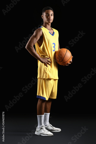 Papel de parede Young African-American basketball player on dark background