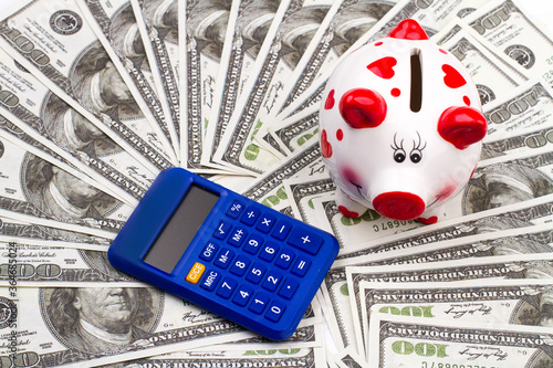 Calculator and piggy bank laying on pile of money. Concept saving and investment money. © DenisProduction.com