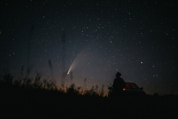 Young man on the background of the starry sky and comet NEOWISE. Comet C / 2020 F3 NEOWISE Observation