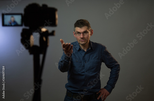 Fényképezés actor wearing glasses in grey shirt with interrogative look stretches hand ahead