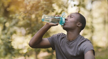 Young Black Man Drinking Water From Sport Bottle At Park
