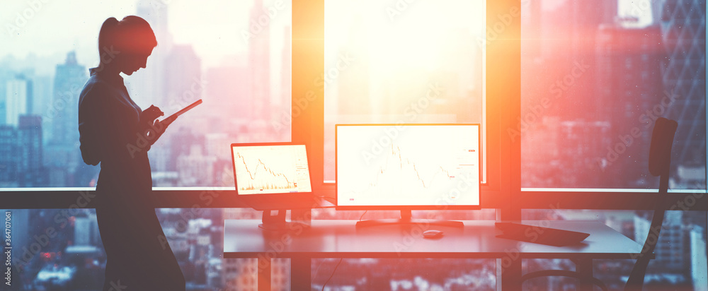 Fototapeta Silhouette of female office employee standing near window with panoramic city views while working on touch pad near mock up PC computer and laptop with financial graphs, Flare effect. Success concept