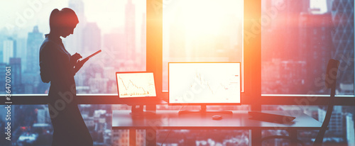Photo Silhouette of female office employee standing near window with panoramic city views while working on touch pad near mock up PC computer and laptop with financial graphs, Flare effect