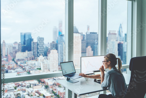 Back view of business woman sitting at panoramic skyscraper office desktop front PC computer with financial graphs and statistics on monitor Fotobehang