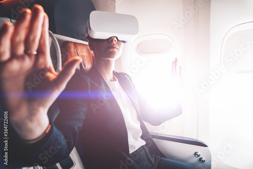 Valokuva Young woman in suit wearing virtual reality headset in airplane and gesturing with hands to control simulation of 3D futuristic dimension