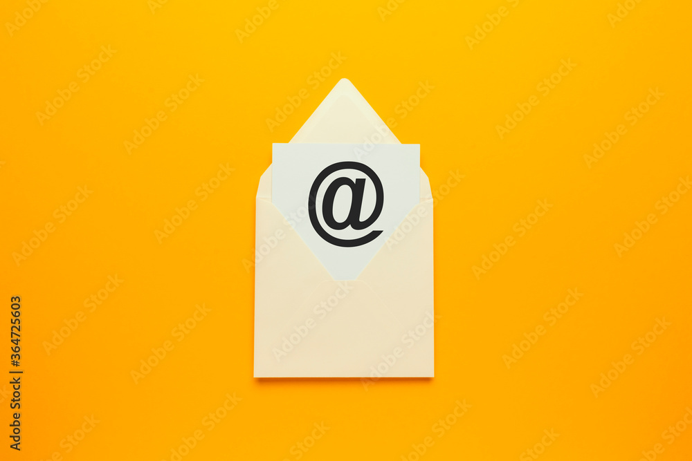 Fototapeta Envelope with e-mail symbol on yellow background, concept of corporate communication and marketing mailings.