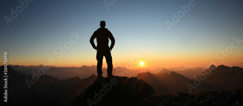 Man Silhouette reaching summit enjoying freedom and looking towards mountains sunset Fototapeta