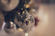 canvas print picture bauble hanging from a decorated Christmas tree. Retro filter effect