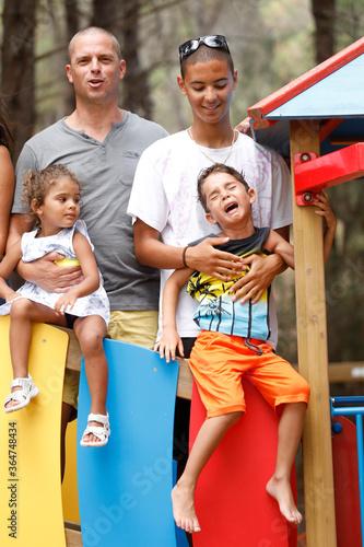 Fotografie, Obraz Padre bianco sta sopra una struttura colorata  con i tre figli mulatti, mentre u