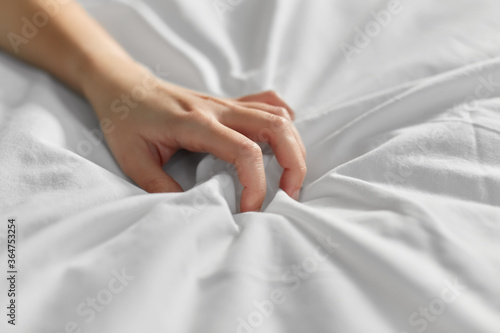Fényképezés bedtime, sex and rest concept - hand of woman squeezing white bed sheet