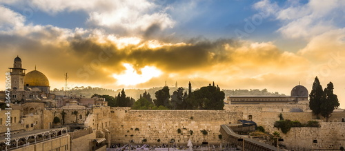 Fototapeta premium Beautiful sunrise clouds over the Mount of Olives and the Temple Mount sites: Dome of the Rock, Western Wall and Al Aqsa Mosque; with Jewish people praying in sections because of covid-19 regulations