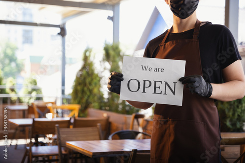 Obraz The waiter works in a restaurant in a medical mask, gloves during coronavirus pandemic. Representing new normal of service and safety. Holding board with words WE ARE OPEN. Taking care of clients. - fototapety do salonu