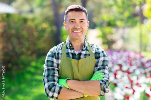 gardening and people concept - happy smiling middle-aged man in apron with cross Canvas