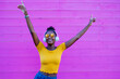 canvas print picture - black woman dancing and smiling, pink background in contrast with yellow clothes and jeans, afro fashion girl with headphones to listen to music, silent disco and new normal, social distancing