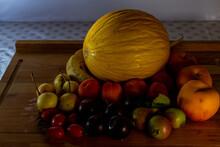 Frutas Frescas De Estación Sobre Mesa De Madera Con Melon, Peras, Tomates, Duraznos, Ciruelas Y Damascos