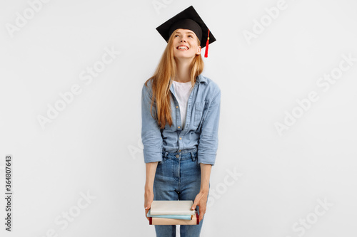 Obraz na plátně Pensive beautiful graduate in a graduation cap on her head, with books in her hands, stands on a white background