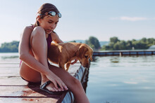 Girl Sitting On The River Dock...