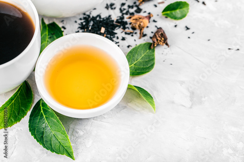 Fotografía Herbal tea, cups and teapot with leaves on grey concrete background