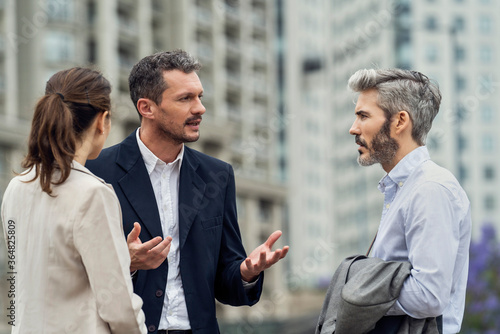 Businesspeople talking in city - 364825809