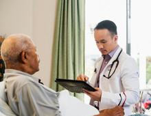 Doctor Using Tablet While Visiting Senior Man In Nursing Home
