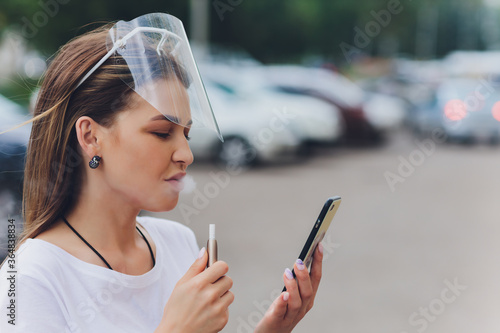 Woman holds an electro cigarette protective face shield. Canvas Print