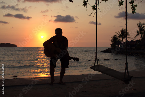 Photo Man reaching for a low note on an acoustic guitar at sunset